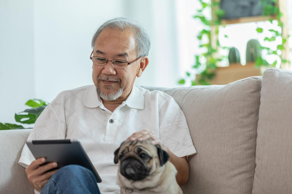 The Lodge at Stephens Lake   Senior man reading tablet on couch next to dog